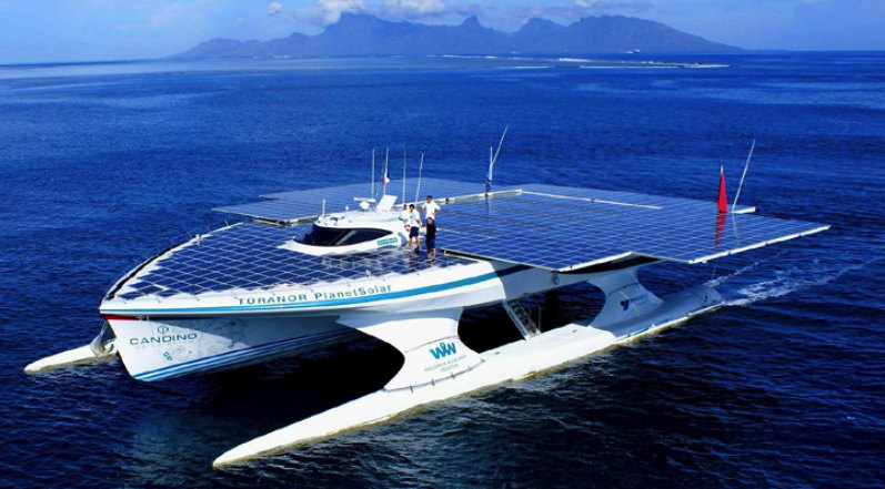 A huge electric ship covered with solar panels sails with mountains n the background