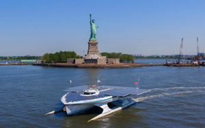 Turanor solar ship sails past the Statue of Liberty