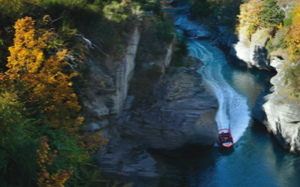 an aerial view of a jetboat going through the narrow Shotover canyon