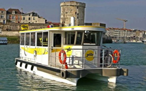 A small 20 passenger solar electric ferry with the castle walls of La Rochelle behind