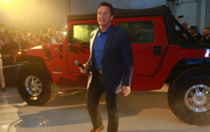 Arnold Schwarzenegger stands in front of an electric HUmmer HI