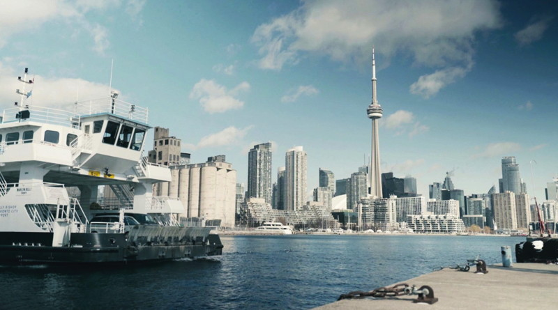 The bow of the battery-powered ferry with Toronto's CN Tower in the background