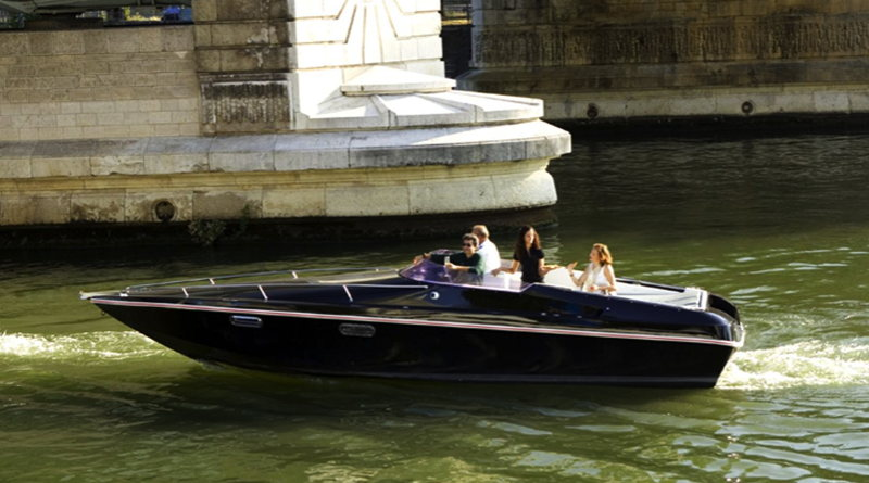 an electric runabout goes along the Seine under a bridge