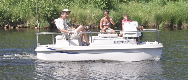 Electric poat going along a river with 4 people aboard enjoying themselves