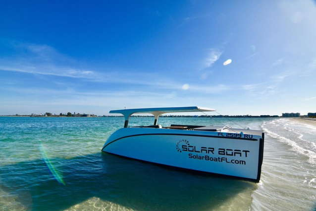 Solar boat with solar panels on the roof anchored on a beach in Florida