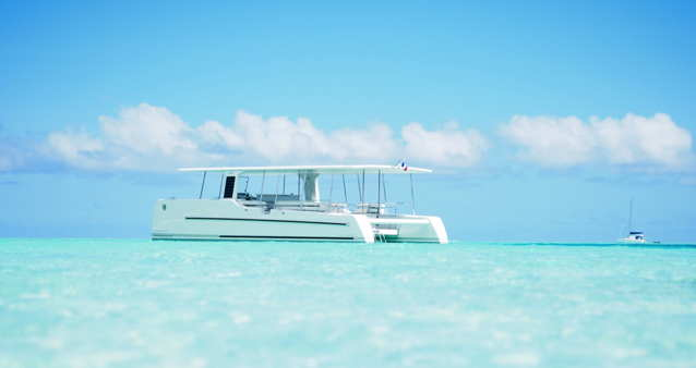 Solar electric catamaran in a beautiful aquamarine sea