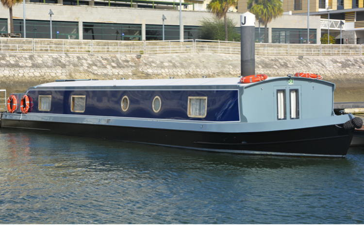 An electric widebeam canal boat in a Lisbon marina
