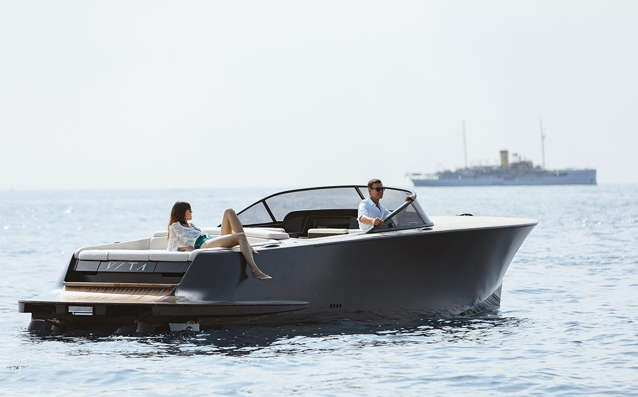 Classic European runabout electric boat with a superyacht in background