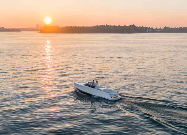 Electric boat on the water with a sunset
