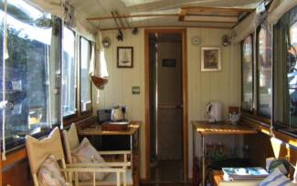 interior of electric narrowboat with narrow door and seats in living area