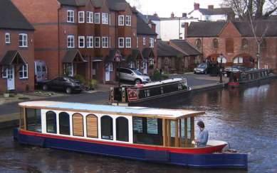 electric narrowboat - blue hull with red trim, on canal with local homes in background