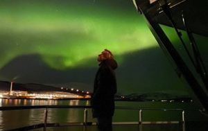 Man on the deck of the arctic eco-cruiser with green Aurora Borealis in sky behind