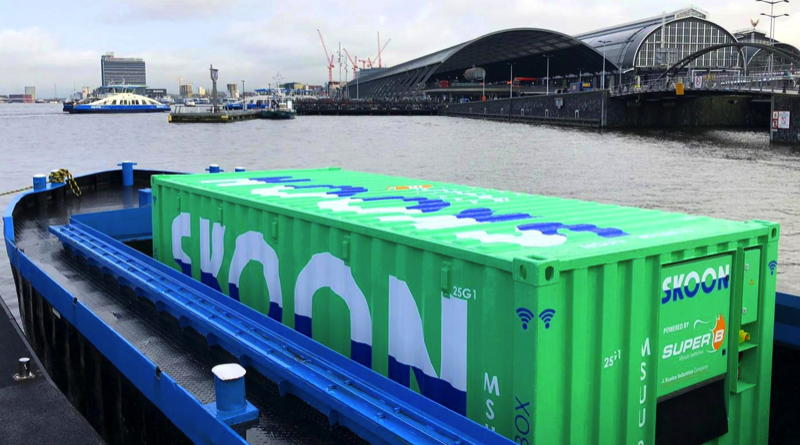 Amsterdam floating battery terminal is a green cargo container on a barge. Port of Amsterdam is in background of photo