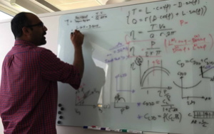 engineer at whiteboard looking at equations about electric flying boat
