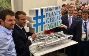 Hydrogen ship captain Eroussard with French President Emannuel Macron and a sign saying 'Make our planet great again'