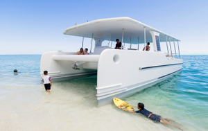 solar electric yacht on sandy beach with family swimming and snorkeling