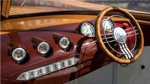 hydrofoiling electric boat has dashboard with wood steering wheel and gauges similar to a 1950s car interior