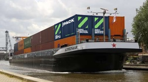 shipper container battery with other containers as the barge Alphenaar goes along canal