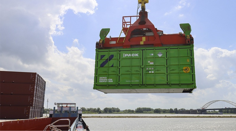 shipping container batteries being loaded by crane onto a barge