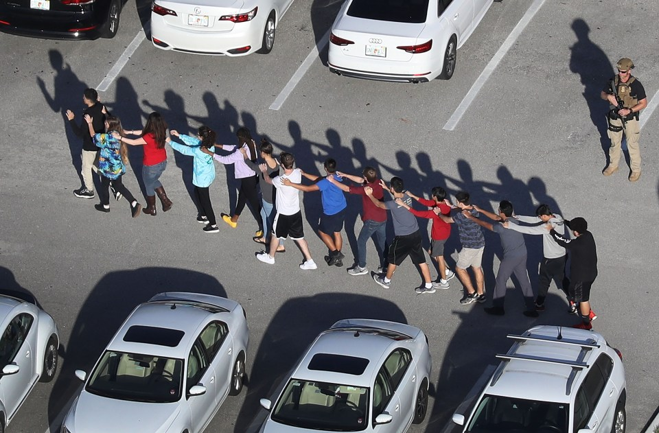 Alumnos siendo escoltados fuera de la escuela tras masacre en Florida