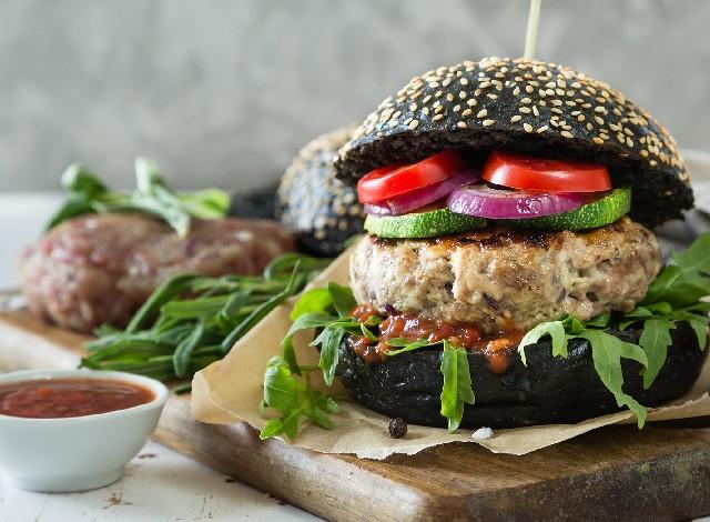 Hombre come la 'hamburguesa más grande del mundo' frente a una protesta vegana