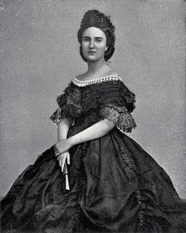 Charlotte en robe du soir, une magnifique crinoline noire dont les manches sont ornées d'engageantes. La coiffure très élaborée de la princesse est devenue sa marque de fabrique.