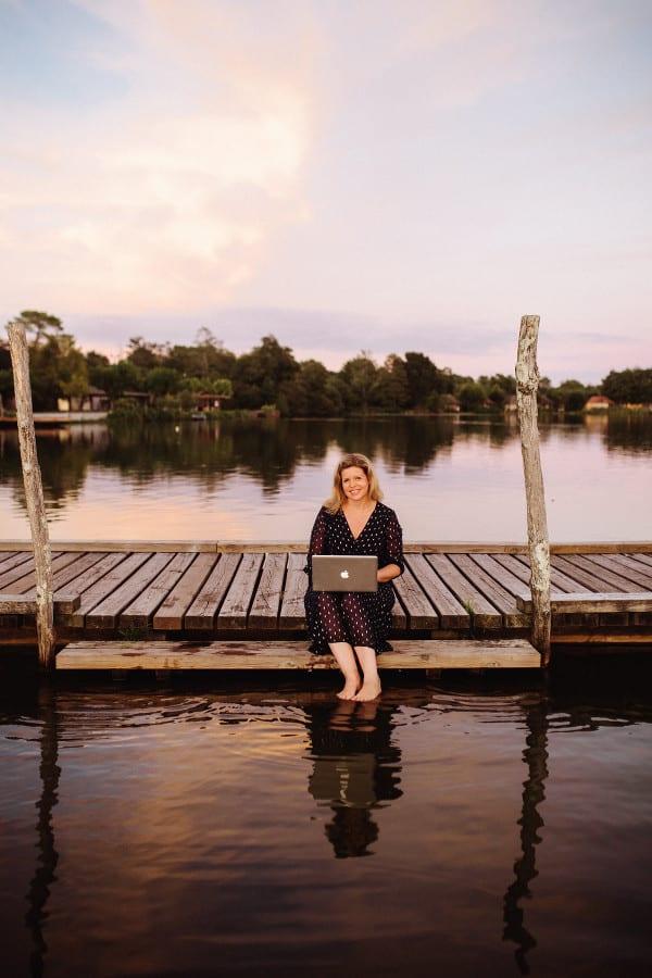 Claire écrit sur son ordinateur portable, assise sur un ponton au bord du lac
