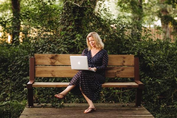 Claire assise sur un banc en train d'écrire sur son ordinateur portable