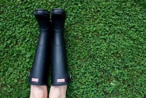 Legs of a white woman in black Wellington boots stretched out in a field of green clover