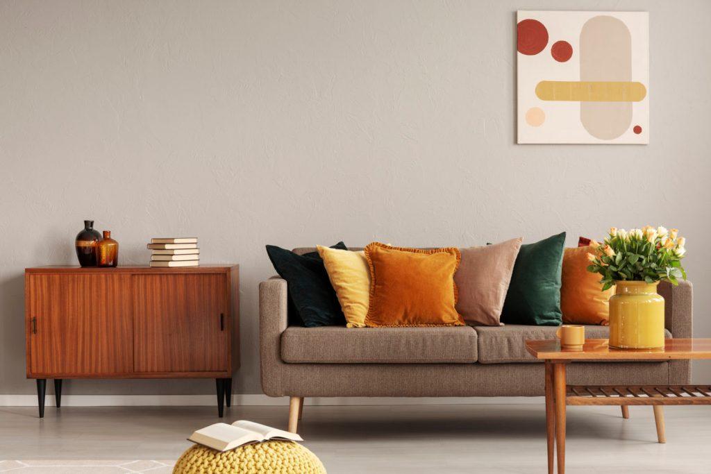 mid-century style beige sofa with autumn toned velvet cushions and yellow vase