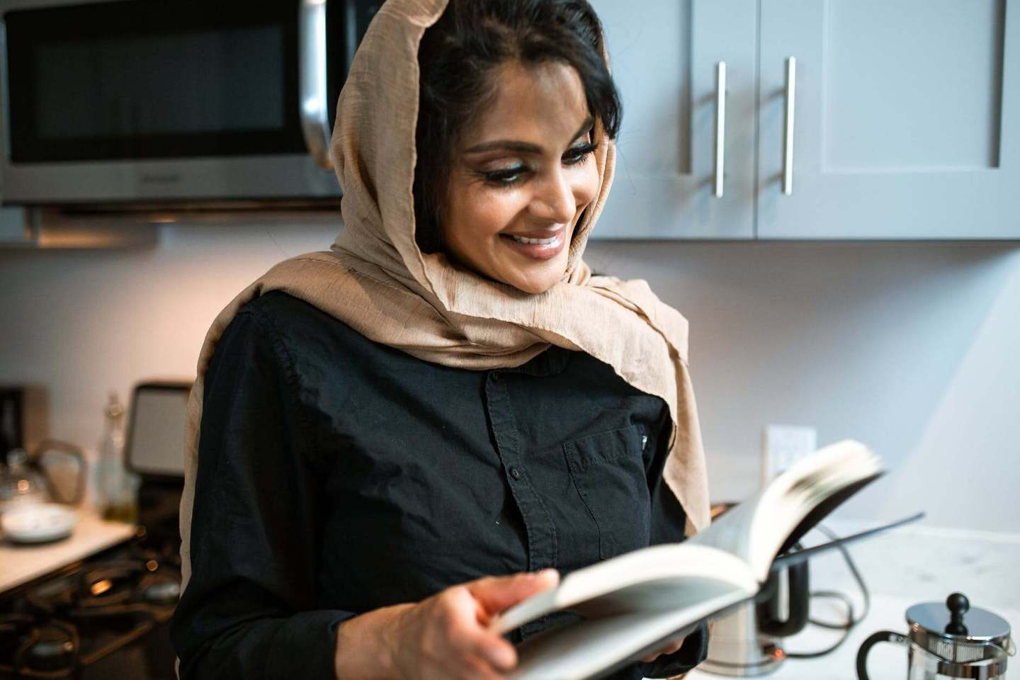 woman in brown hijab holding white tablet computer