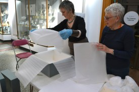 Two women placing tissue paper in a box