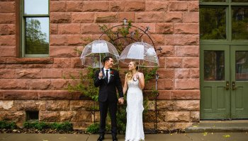 Bride and groom pose for their rainy Flagstaff Courthouse wedding by Flagstaff wedding photographer PMA Photography.