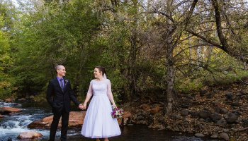 Bride and groom pose for their L'Auberge de Sedona wedding by Sedona wedding photographer PMA Photography.