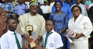 L-R: Oyo State Governor, Senator Abiola Ajimobi (second row) presents trophy of first position to Lagelu Grammar School, Ibadan; Commissioner for Women Affairs, Social Development and Poverty Alleviation, Mrs Atinuke Oshunkoya; and the ministry's Permanent Secretary, Mrs Folusho Sali, at this year's Children day march past held at the Lekan Salami Stadium, Ibadan...on Saturday