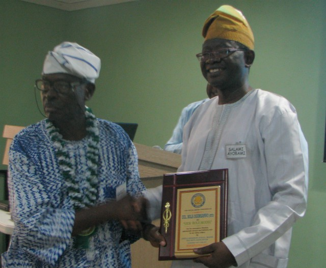 Colonel Bola Ogunsanwo, being handed a plaque to confirm his position as 'Mentor' of the Class set by Professor Ayobami Salami, the chairman of the set's School's Liaison Committee. He is also the Vice Chancellor of The Technical University, Ibadan (Tech-U)