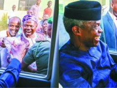 ...Vice President Yemi Osinbajo being given a loaf of bread by enthusiastic Abuja resident...