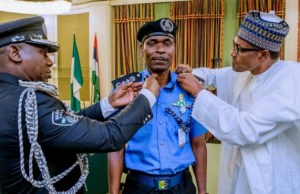 Mr Abubakar Mohammed Adamu, the new Acting IGP being decorated by President Muhammadu Buhari, right...