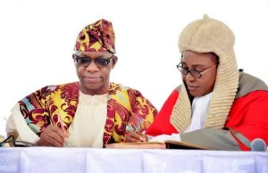 Governor Dapo Abiodun, left, signing to 'resume duties' as the Governor of Ogun State...on Wednesday...