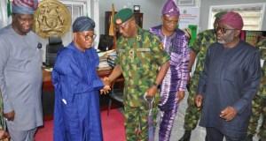 The GOC, Major General Okwudili Fidelis Azinta in a handshake with Osun State Governor, Alhaji Isiaka Adegboyega Oyetola in the governor's office, Osogbo while others look on…