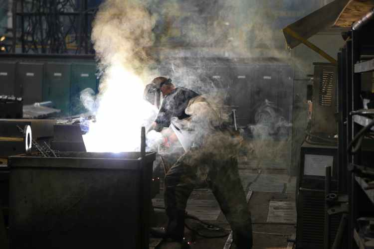 man wearing welding mask covered in welding smokes