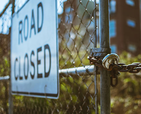 Road closed sign on a chained fence