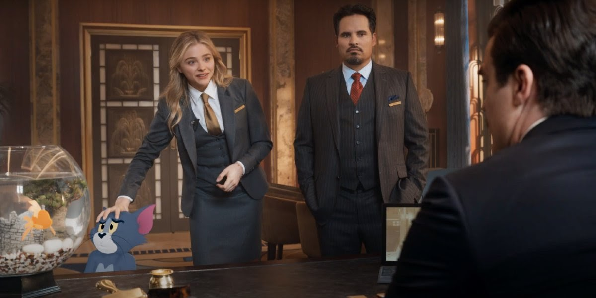 Kayla (Chloë Grace Moretz) and Terence (Michael Peña) speaking with Mr. Dubros (Rob Delaney)
