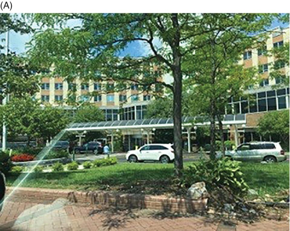 Photo displaying a front view of a hospital. Trees and cars are observed in the front.