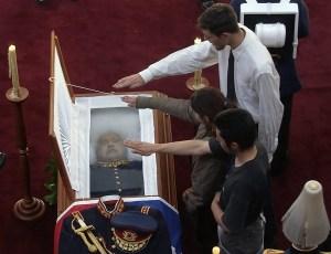 SCH02 - SANTIAGO (CHILE), 11/12/06.- Jóvenes hacen el saludo nazi frente al ataúd del ex dictador chileno Augusto Pinochet Ugarte hoy, lunes 11 de diciembre, mientras es velado en la Escuela Militar del Libertador Bernardo O'Higgins. Pinochet murió a la edad de 91 años ayer, 10 de diciembre de 2006, a las 14:15 horas (17:15 GMT), en el Hospital Militar tras estar una semana afectado de una infarto al miocardio y un edema pulmonar. De acuerdo a lo comunicado oficialmente por el Gobierno y el Ejército, Pinochet no recibirá honores de Estado en su funeral, pero el Ejército le rendirá los honores que su reglamento dispone para los ex comandantes en jefe. La misa fúnebre está fijada para el mediodía del martes y posteriormente, el cadáver de Pinochet será incinerado y sus cenizas entregadas a su familia. EFE/Ian Salas