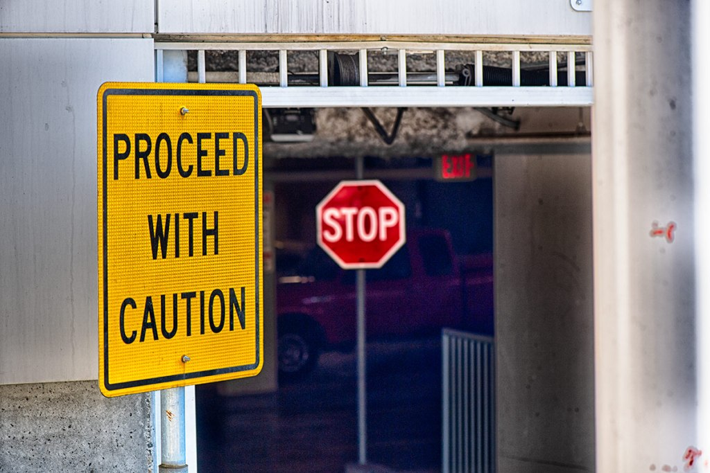 "photo of 2 signs, one says ""proceed with quation"" the other says ""stop"""