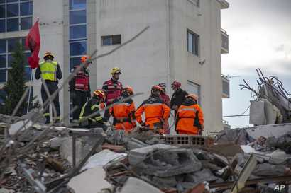 Rescuers from France and Switzerland operate at a collapsed building after the 6.4-magnitude earthquake in Durres, western Albania, Nov. 29, 2019.