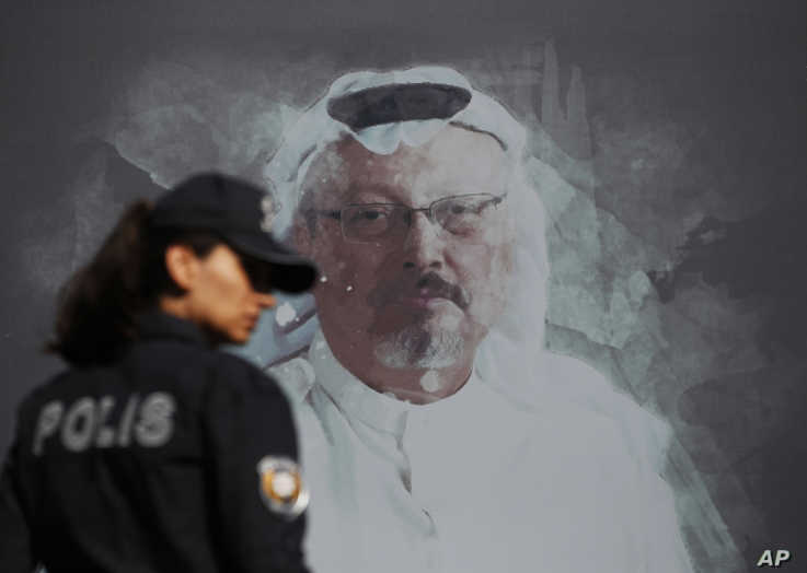A Turkish police officer walks past a picture of slain Saudi journalist Jamal Khashoggi prior to a ceremony, near the Saudi…