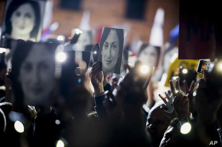 People hold pictures of slain journalist Daphne Caruana Galizia as they protest outside the office of the Maltese Prime…