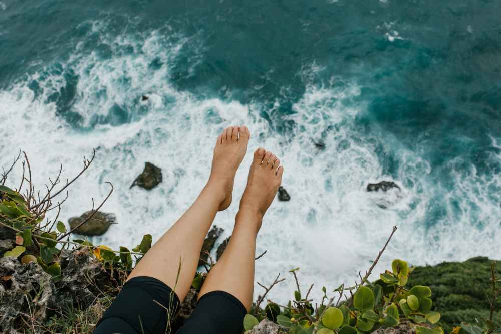 woman sitting on edge of cliff above foaming sea